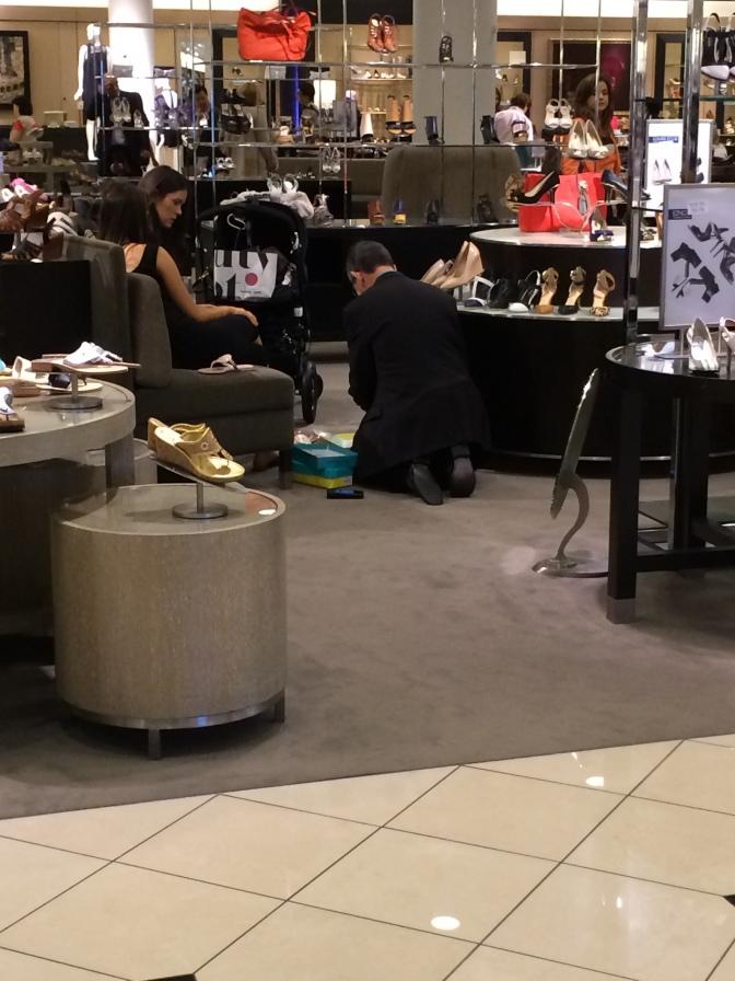 Naiset kenkämyyjän palveltavana.