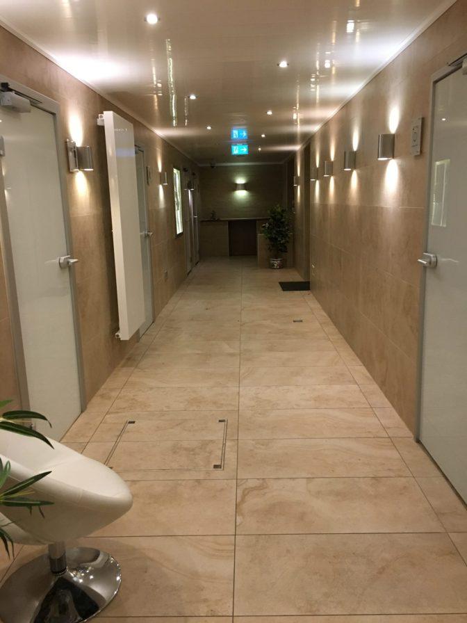 Mun selän takana oli tiskauspaikka (huom! lämmitetyssä tilassa) ja tuolla käytävän päässä oli suihkutilat.